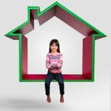Kleines asiatisches Mädchen, das auf virtuellem Haus 3D sitzt Stockbilder