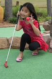 Kleines asiatisches Mädchen, das Minigolf spielt Stockfotos