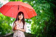 Kleines asiatisches Mädchen mit Regenschirm Stockbild