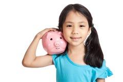 Kleines asiatisches Mädchenlächeln mit Sparschwein Stockfotos