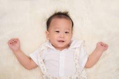 Kleines asiatisches Säuglingsbaby, das mit glücklichem Gesicht lächelt Stockbilder