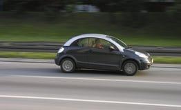 Kleines Auto, das auf eine Datenbahn beschleunigt Stockfoto