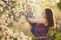 Kleines Baby auf Händen der Mutter Frau, die mit Kind draußen spielt Stockfotografie