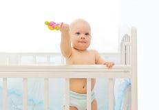 Kleines Baby, das auf Betthaus mit Spielzeug spielt Lizenzfreie Stockfotos