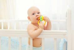 Kleines Baby, das auf Betthaus mit Spielzeug spielt Stockbild