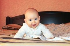 Kleines Baby, das auf dem Bett lächelt Stockfoto
