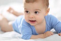 Kleines Baby, das auf dem Bettkriechen liegt Stockbilder