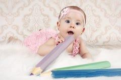 Kleines Baby, das auf dem Boden mit großen Zeichenstiften liegt Lizenzfreie Stockbilder