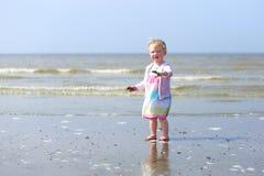 Kleines Baby, das auf dem Strand spielt Stockbilder