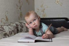kleines Baby, das auf der Couch liegt und in einen Notizbuchstift schreibt Lizenzfreies Stockfoto