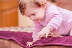 Kleines Baby, das auf der Decke liegt und Zunge zeigt Stockfoto