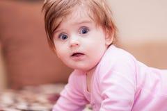 Kleines Baby, das auf der Decke liegt und Zunge zeigt lizenzfreies stockfoto