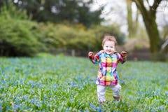 Kleines Baby, das auf einem blauen Blumengebiet geht Stockbild