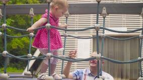 Kleines Baby, das auf einen Seilspielplatz geht stock footage