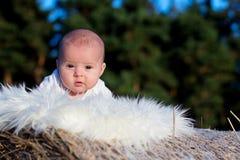 Kleines Baby, das auf Heuschober liegt Lizenzfreies Stockfoto