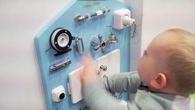 Kleines Baby, das bedacht mit beschäftigtem Brett auf der Wand spielt Nahaufnahme stock video footage