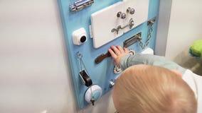 Kleines Baby, das bedacht mit beschäftigtem Brett auf der Wand spielt Nahaufnahme stock footage