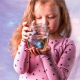 Kleines Baby, das ein fishbowl mit einem blauen Fisch hält Sorgfalt conce Stockfotos
