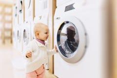 kleines Baby, das eine Waschmaschine betrachtet lizenzfreies stockbild