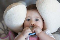 Kleines Baby, das in einem Halskissen mit Abdeckung in den Händen liegt Stockfotografie