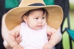 Kleines Baby, das einen übergroßen Hut trägt und auf ihrem Mutter ` s Schoss sitzt Stockbild