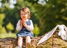 Kleines Baby, das frischen Apfel im Sommerpark isst. Lizenzfreie Stockfotos