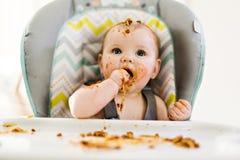 Kleines Baby, das ihr Abendessen isst und eine Verwirrung macht stockfotografie
