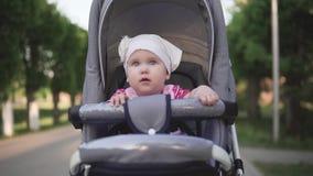 Kleines Baby, das im Kinderwagen sitzt und, Kamera sich bewegt in Richtung zu lächelt stock video footage