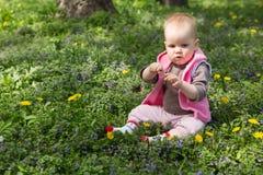 Kleines Baby, das im Park auf dem Gras spielt Lizenzfreies Stockfoto