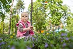 Kleines Baby, das im Park auf dem Gras spielt Stockbild
