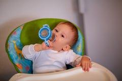 Kleines Baby, das im Stuhl für die Fütterung und Trinkwasser mit sitzt lizenzfreie stockfotos