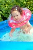 Kleines Baby, das im waterpool spritzt Stockfoto