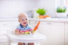 Kleines Baby, das Karotte isst Stockbild