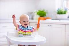 Kleines Baby, das Karotte isst Lizenzfreie Stockfotos