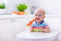 Kleines Baby, das Karotte isst Stockbilder