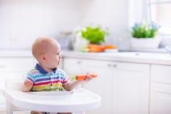 Kleines Baby, das Karotte isst Lizenzfreies Stockfoto