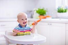 Kleines Baby, das Karotte isst Stockfotografie