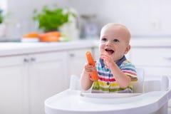 Kleines Baby, das Karotte isst Stockfotos