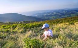 Kleines Baby, das mit Gras in den Bergen im Sommer spielt Stockfotos
