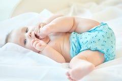 Kleines Baby, das mit seinem Bein spielt Stockfoto