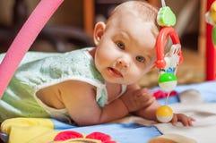 Kleines Baby, das mit Spielwaren spielt Stockbild