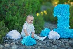 Kleines Baby, das nah an Nummer Eins-Geburtstagszahl-Blaufarbe sitzt Lizenzfreie Stockfotografie