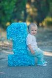 Kleines Baby, das nah an Nummer Eins-Geburtstagszahl-Blaufarbe sitzt Lizenzfreies Stockbild