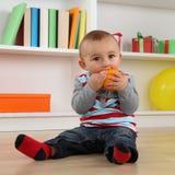 Kleines Baby, das orange Frucht isst Stockfotografie