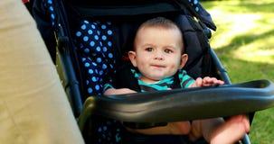 Kleines Baby, das in seinem Pram im Park sitzt stock video footage