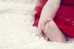Kleines Baby, das seinen Fuß lokalisiert hält Lizenzfreies Stockbild