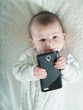 Kleines Baby, das Smartphone im Bett hält Stockfotografie