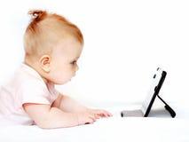 Kleines Baby, das Tabletten-PC auf Weiß verwendet Lizenzfreie Stockfotografie