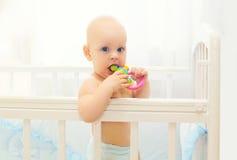 Kleines Baby, das zu Hause auf Bett mit Spielzeug spielt Lizenzfreie Stockfotos