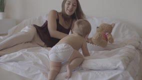 Kleines Baby, das zu Hause auf dem Bett spielt Nette Mutter, die nahe Kind sitzt Reizendes Kind, das auf dem Bett climbling ist K stock video